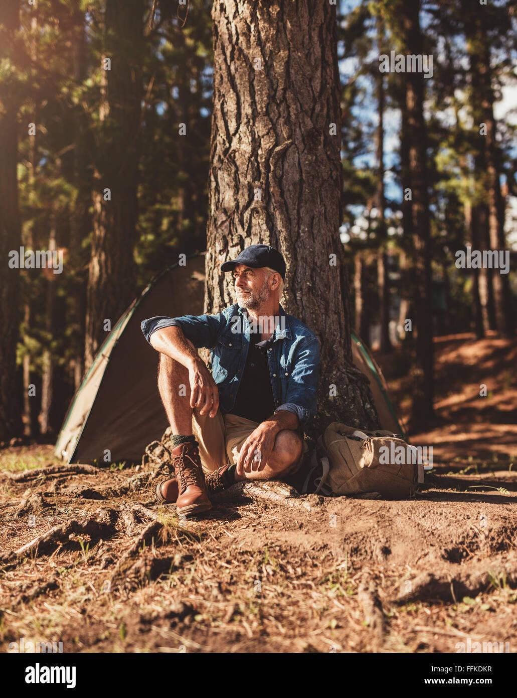 Ritratto di senior uomo seduto da solo da un albero con una tenda in background. Coppia uomo seduto in un campeggio Immagini Stock
