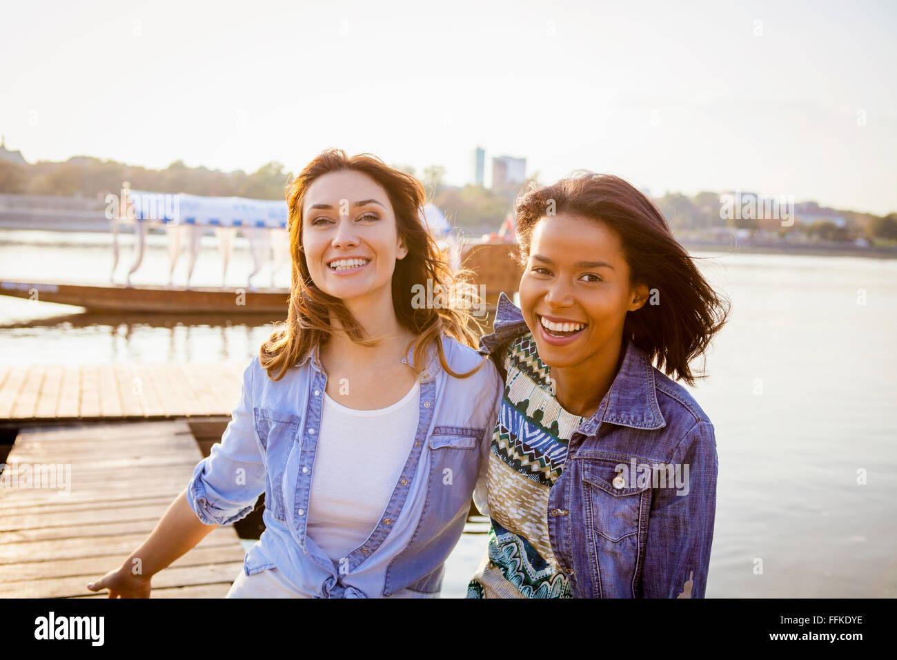 Ritratto di due donne ridere su di una pausa in città Immagini Stock