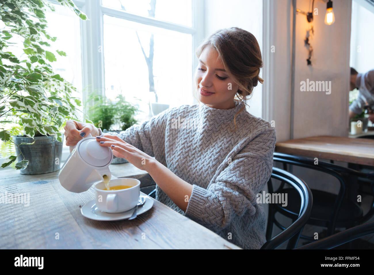 Donna felice bere il tè in cafe Immagini Stock