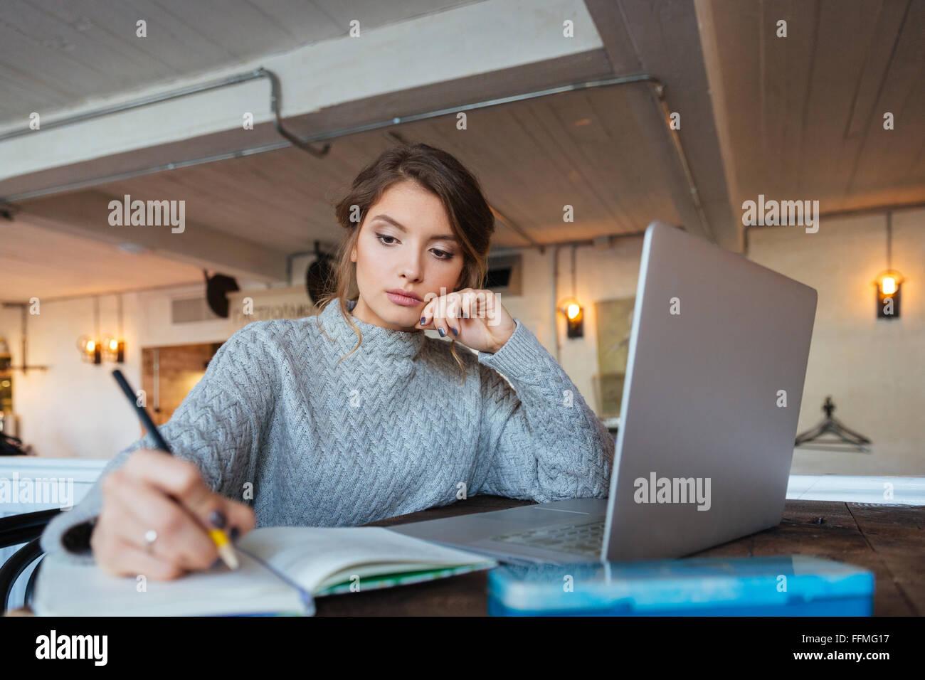 Donna che lavorano con il computer portatile e il blocco note in cafe Immagini Stock