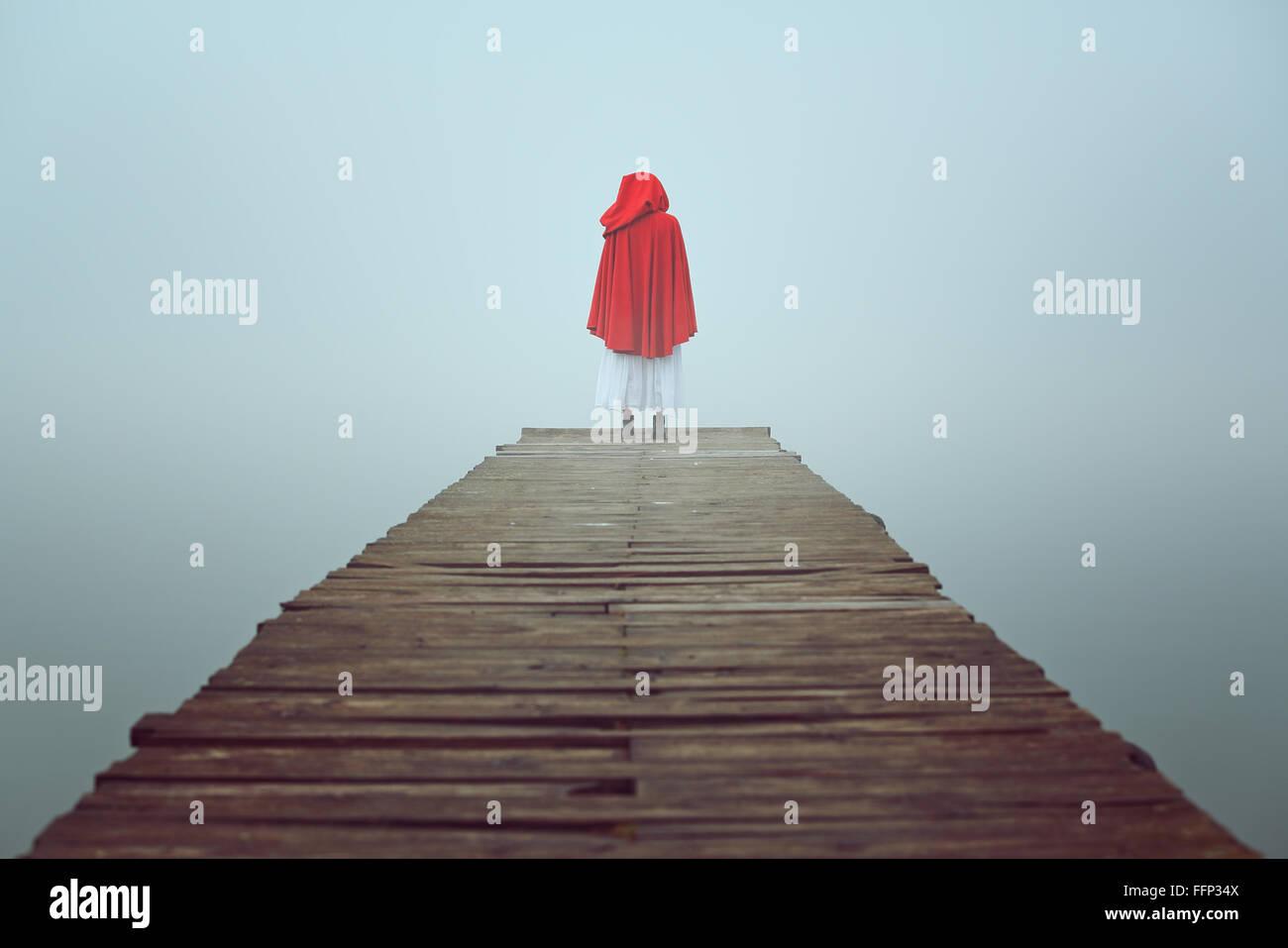 Con cappuccio rosso donna guarda al lago di nebbia su un molo in legno . Tristezza e solitudine concept Immagini Stock