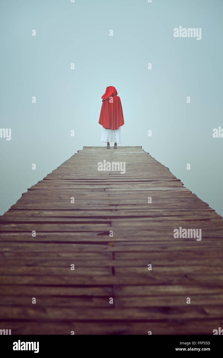 Lone donna vestito rosso con accappatoio con cappuccio in una nebbiosa pier Foto Stock