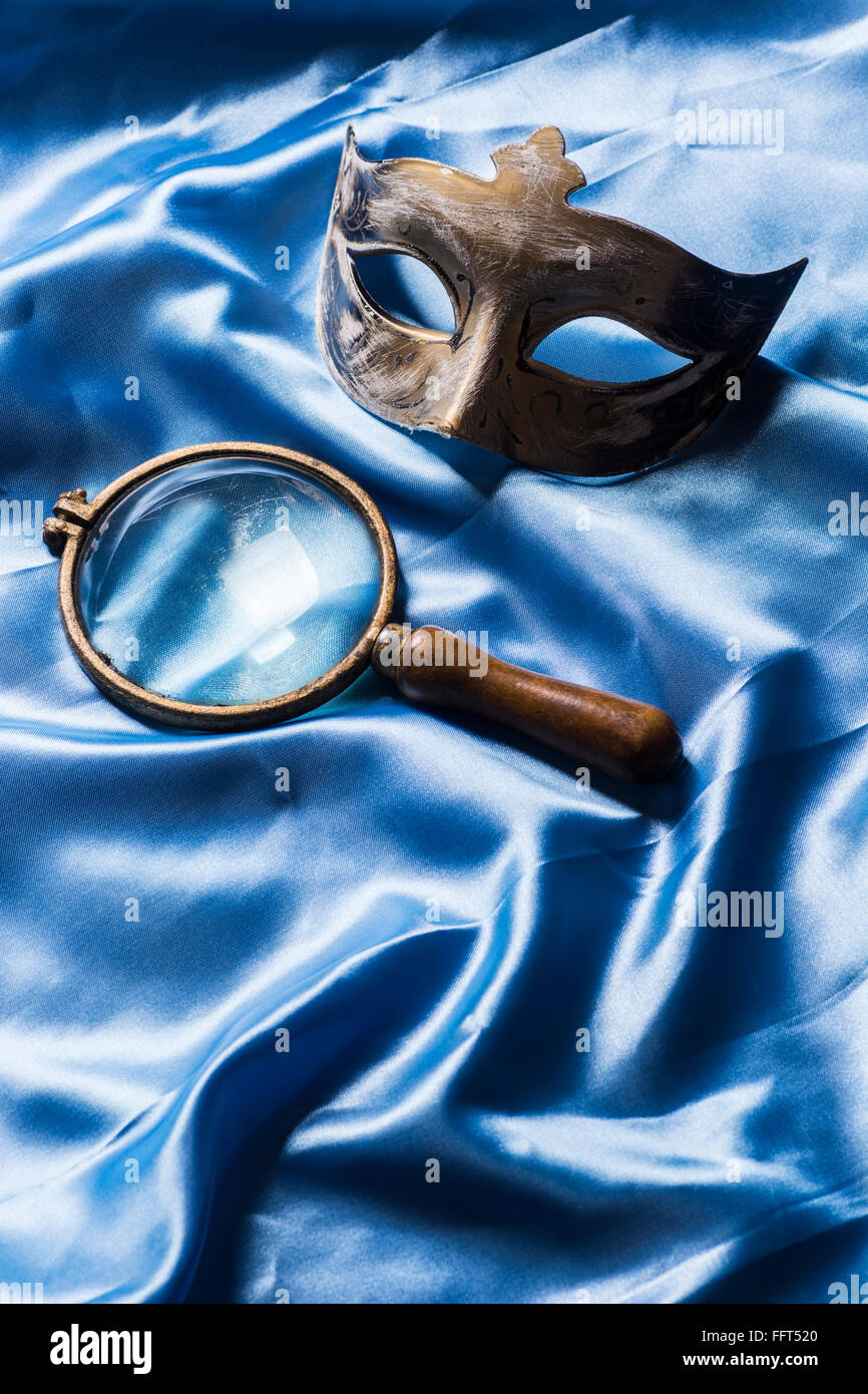 Maschera e un vintage lente di ingrandimento Immagini Stock