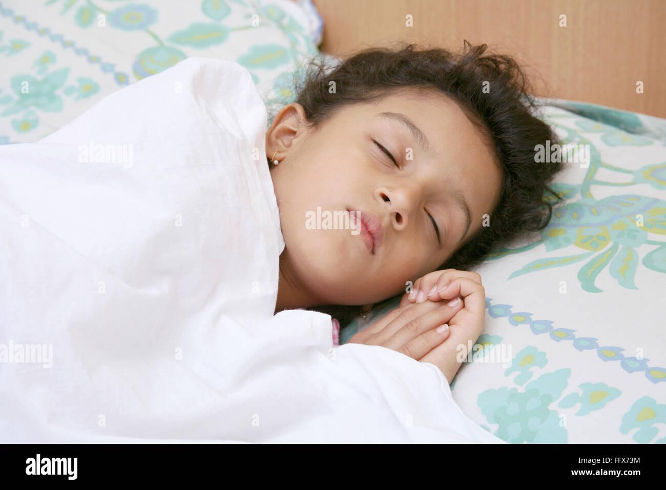 Piccola bambina di 6 anni che dorme tranquillamente sul letto che copre il suo corpo con lenzuolo bianco signor Immagini Stock