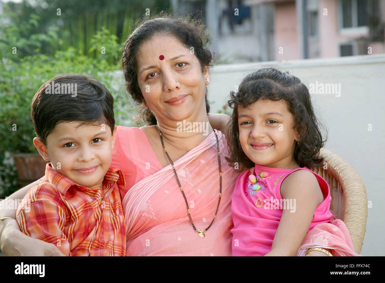 Gran Madre e grand bambini tenendo entrambi i bambini vicino a lei signor # 687F 687G e 687E Immagini Stock