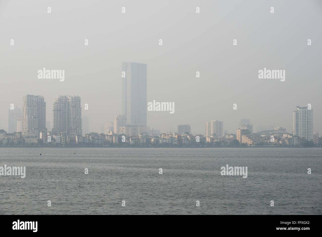 Mist, nebbia o smog inquinamento in un vago skyline di Hanoi visto oltre Westlake, Vietnam, Gennaio Immagini Stock