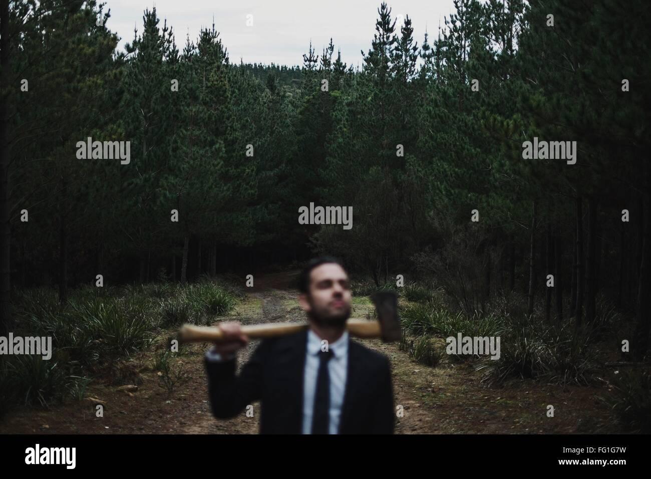 Uomo in tuta Holding Ax nella foresta Immagini Stock