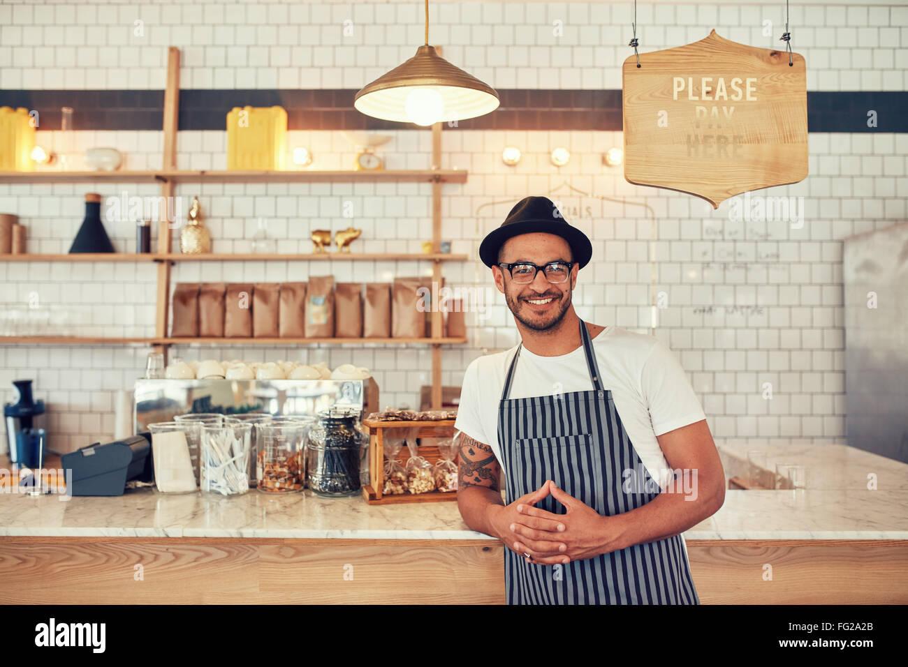 Ritratto di felice giovane uomo che indossa un grembiule e hat appoggiandosi a un contatore cafe. Barista maschio Immagini Stock