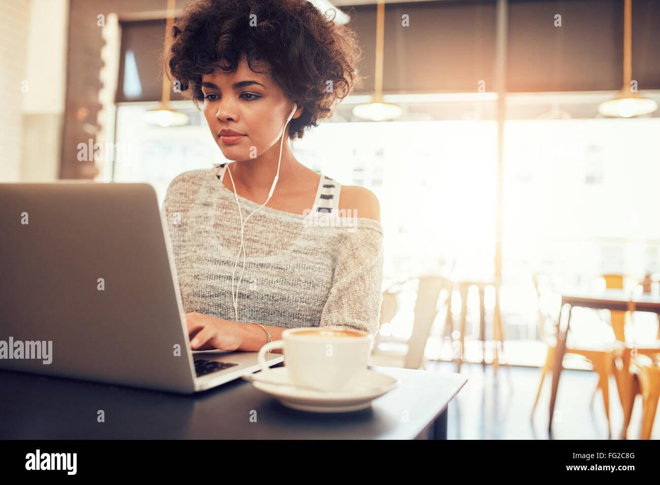 Ritratto di giovane e bella donna con gli auricolari lavorando sul computer portatile mentre seduto a un coffee Immagini Stock