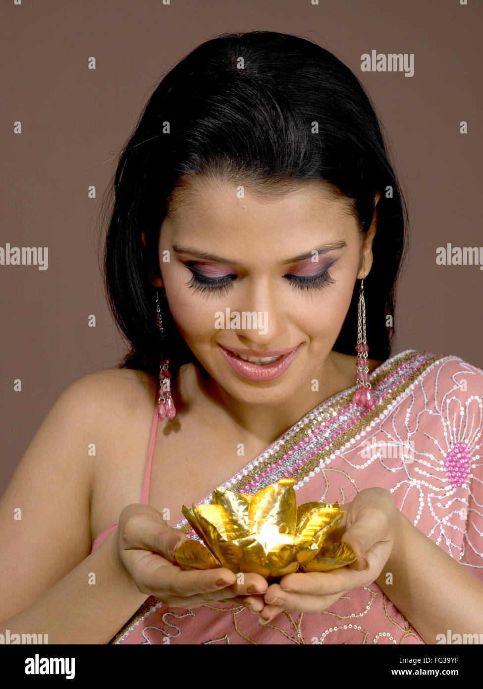South Asian Indian donna sorridente e di colore dorato diya su mano palme signor # 702 Foto Stock