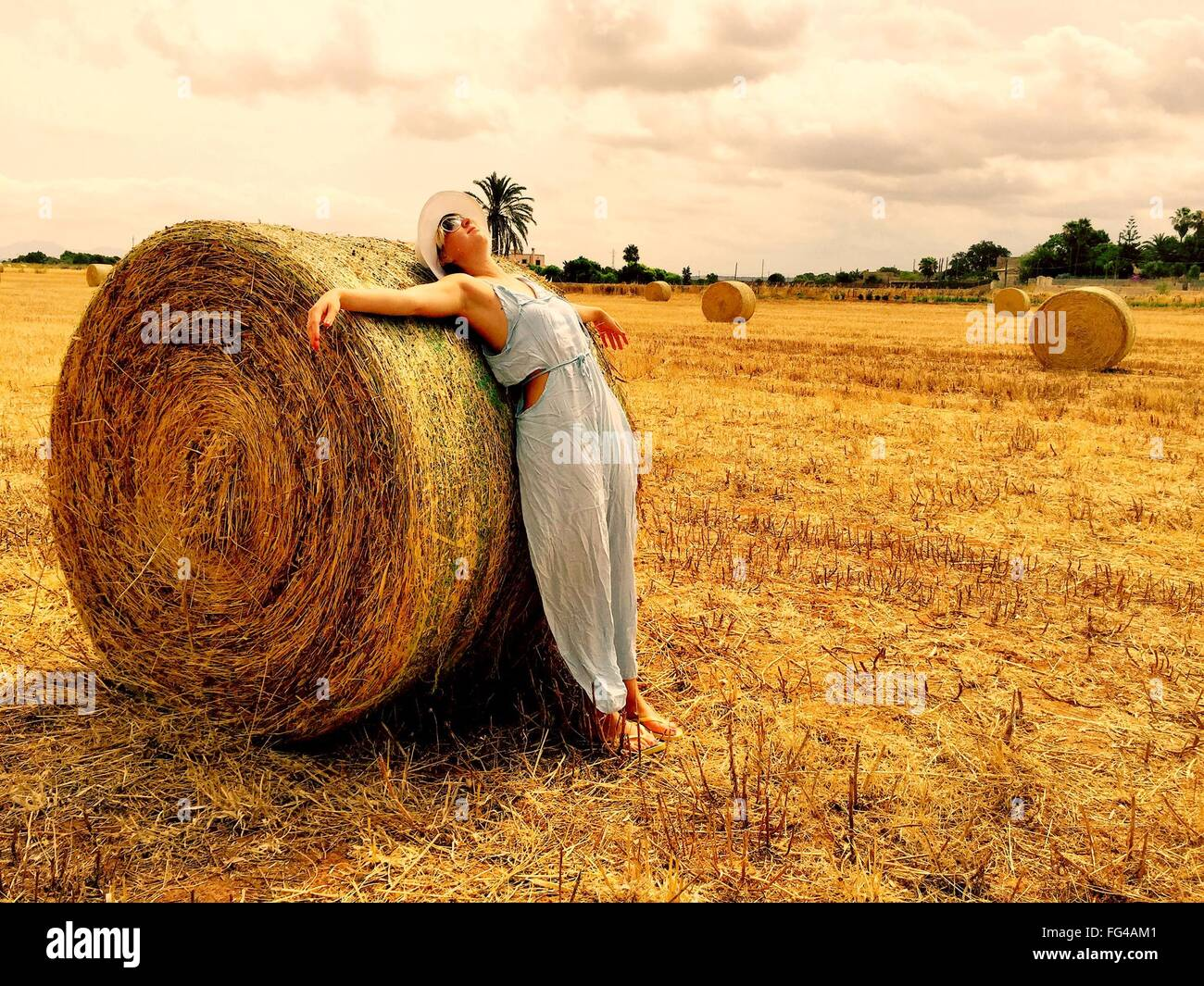 Donna appoggiata sulla balla di fieno in campo contro il cielo nuvoloso Immagini Stock