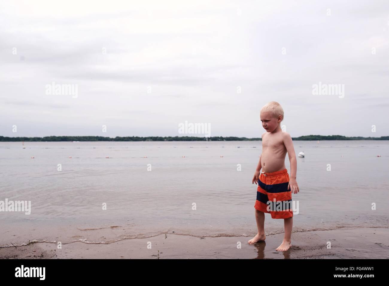 Ragazzo in piedi sulla riva del mare contro Sky Immagini Stock
