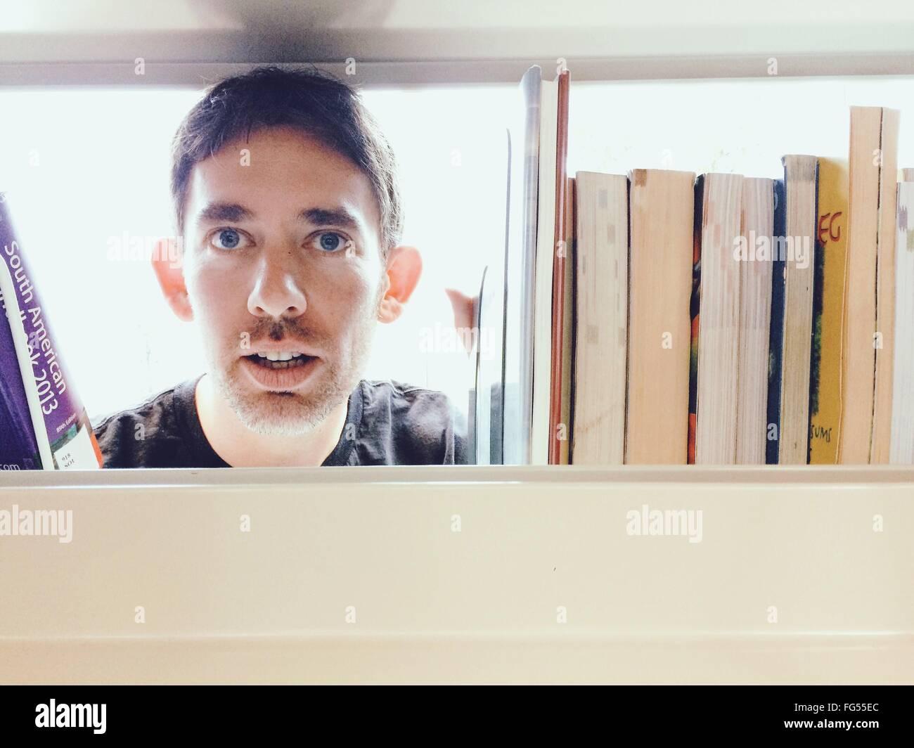 Ritratto di uomo prendendo Prenota da scaffale in libreria Immagini Stock