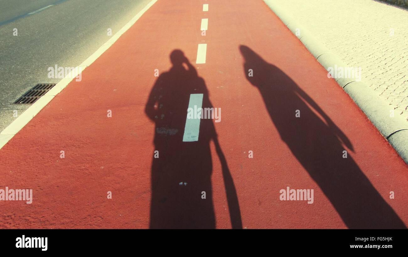 L uomo e la donna ombra su strada Immagini Stock