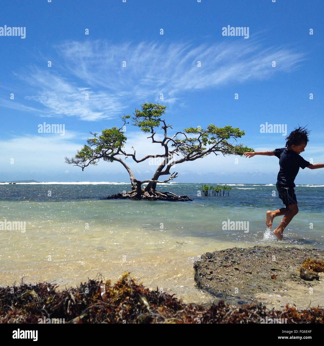 Wet giocoso ragazzo in spiaggia contro Sky Immagini Stock