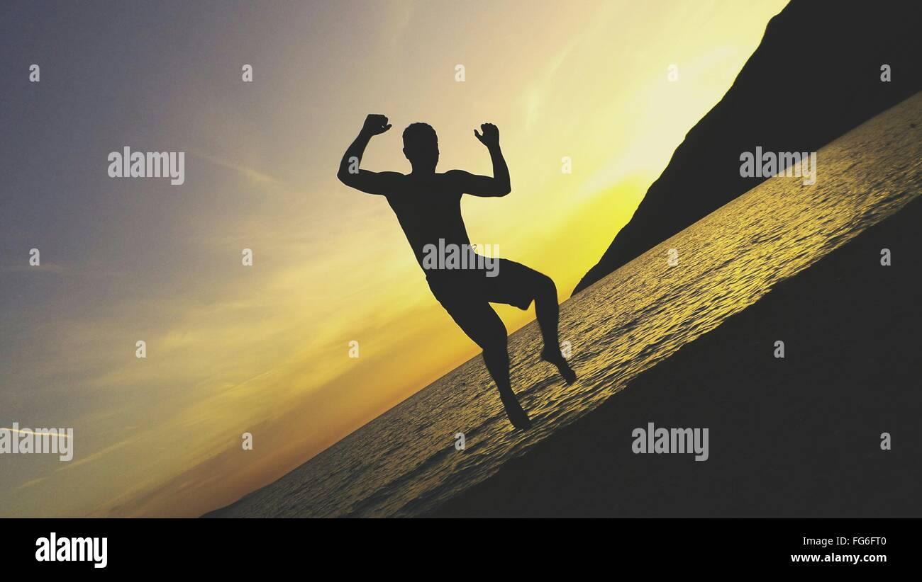 Immagine di inclinazione di Silhouette uomo saltando al Beach contro Sky durante il tramonto Immagini Stock