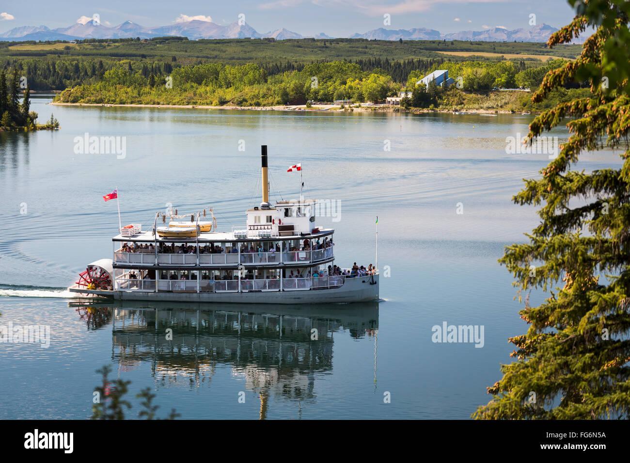 Pedalo' barca sul lago con viale alberato costa, colline e montagne sullo sfondo e il cielo blu e nuvole; Calgary, Immagini Stock