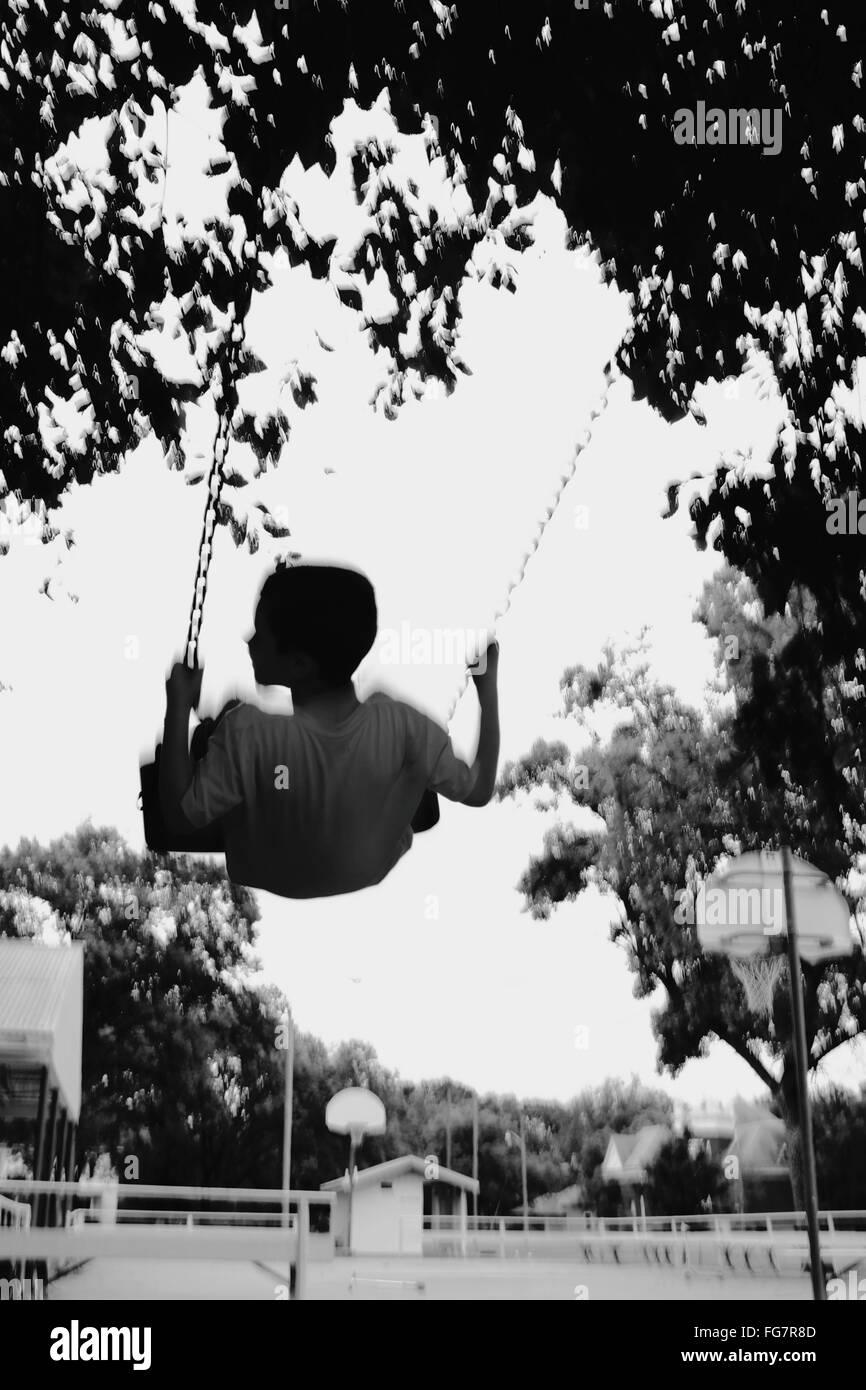 Movimento sfocate di Boy godendo sull'altalena nel parco giochi Immagini Stock