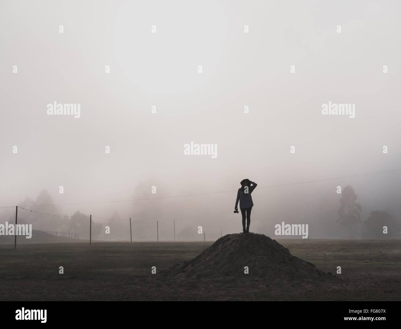 Silhouette donna in piedi sul mucchio nel nebbioso Meteo Immagini Stock