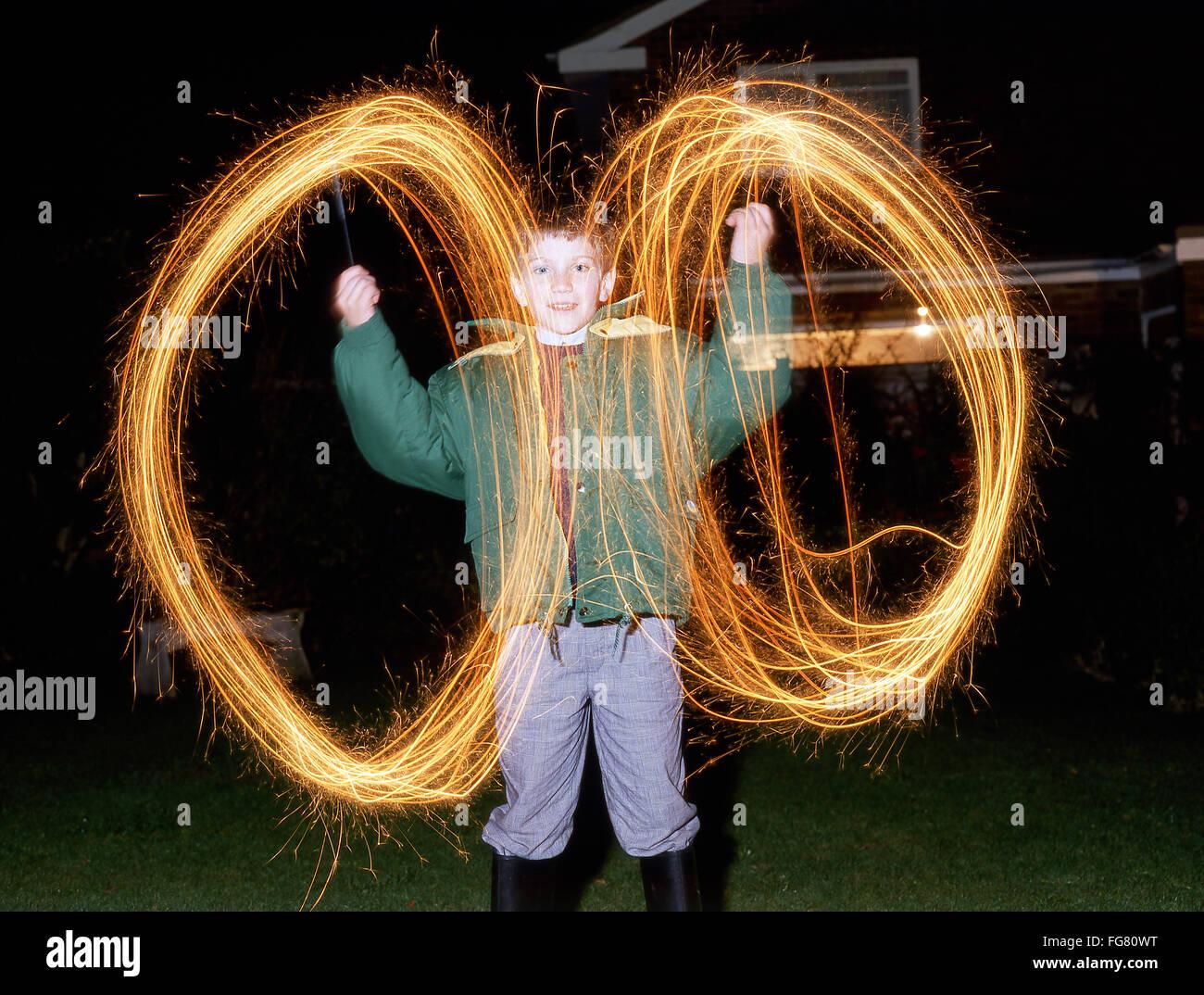 Giovane ragazzo che cerchi con botti sulla notte di fuochi d'artificio, Berkshire, Inghilterra, Regno Unito Immagini Stock