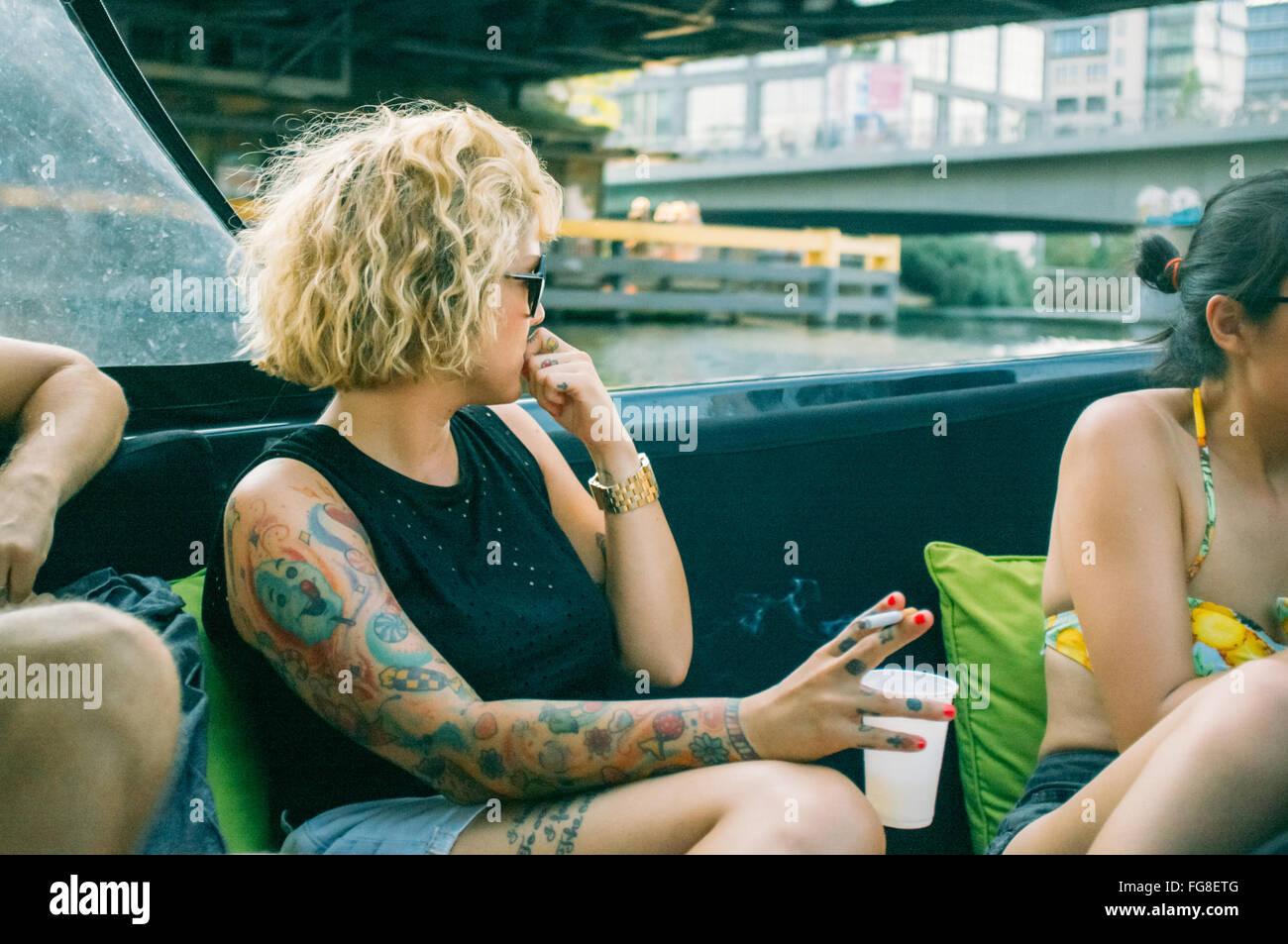 Le donne sedute e godendo in barca nel fiume Immagini Stock