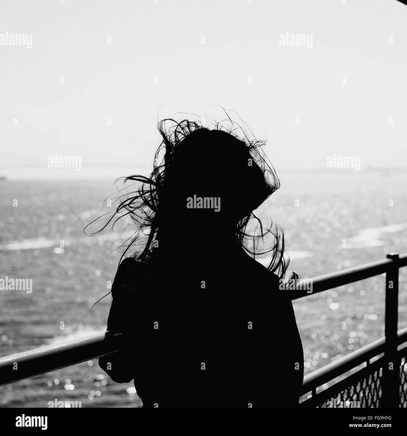 Vista posteriore di Silhouette donna in piedi alla ringhiera di protezione contro il mare Immagini Stock