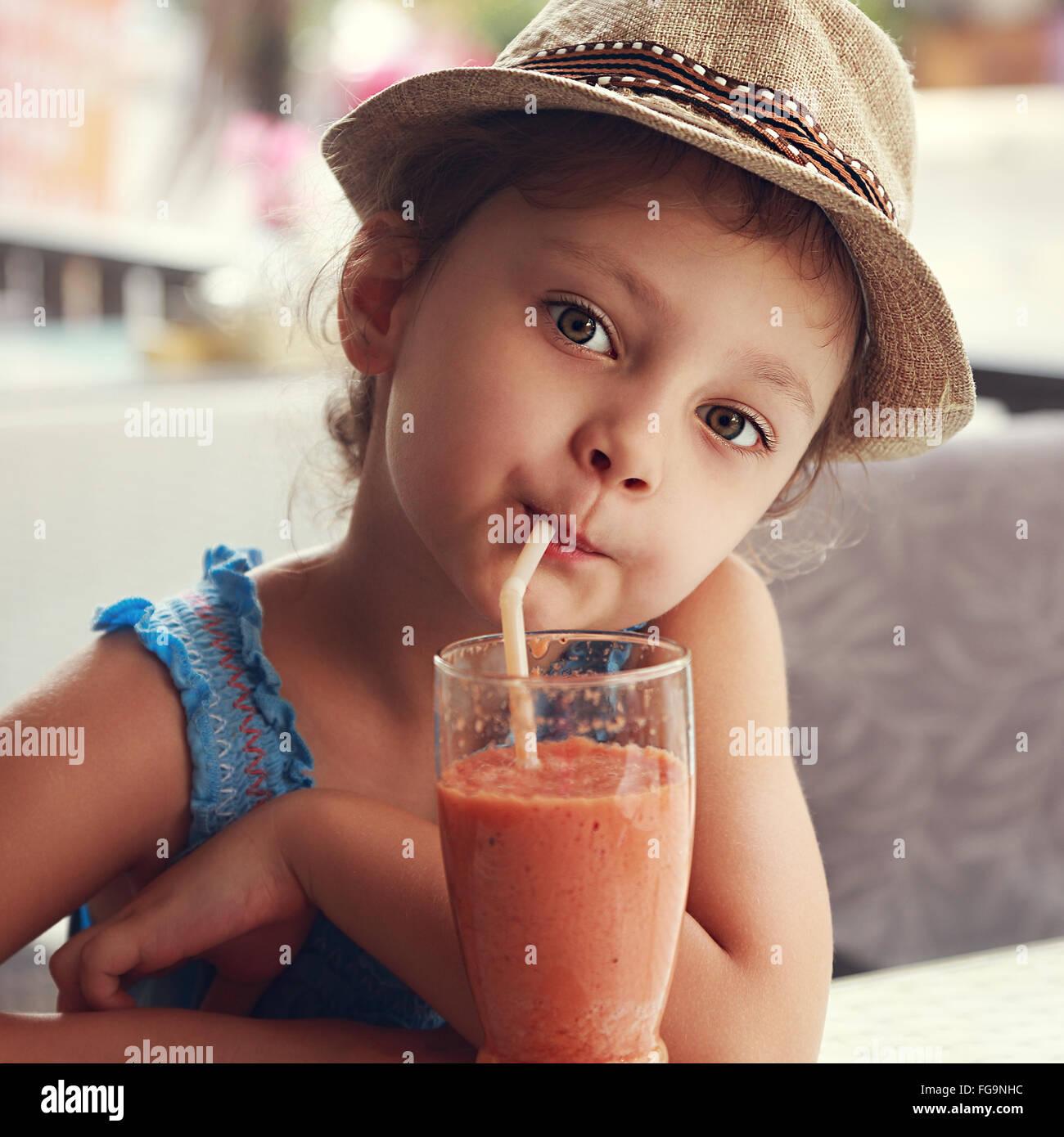 Divertimento carino kid ragazza bere il frullato sano succo in street restaurant. Closeup tonica ritratto Immagini Stock