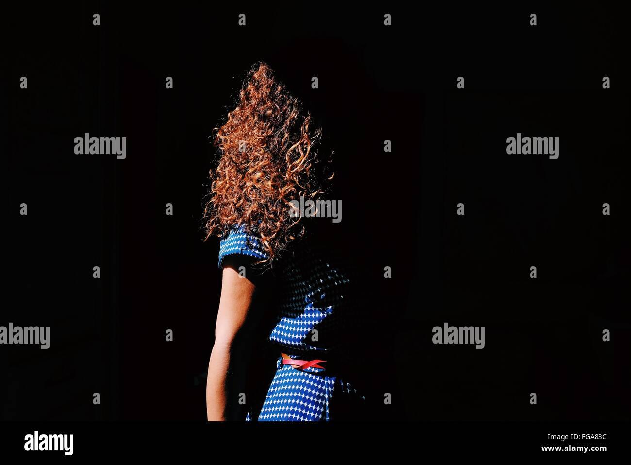 Marrone capelli ricci donna in presenza di luce solare Immagini Stock