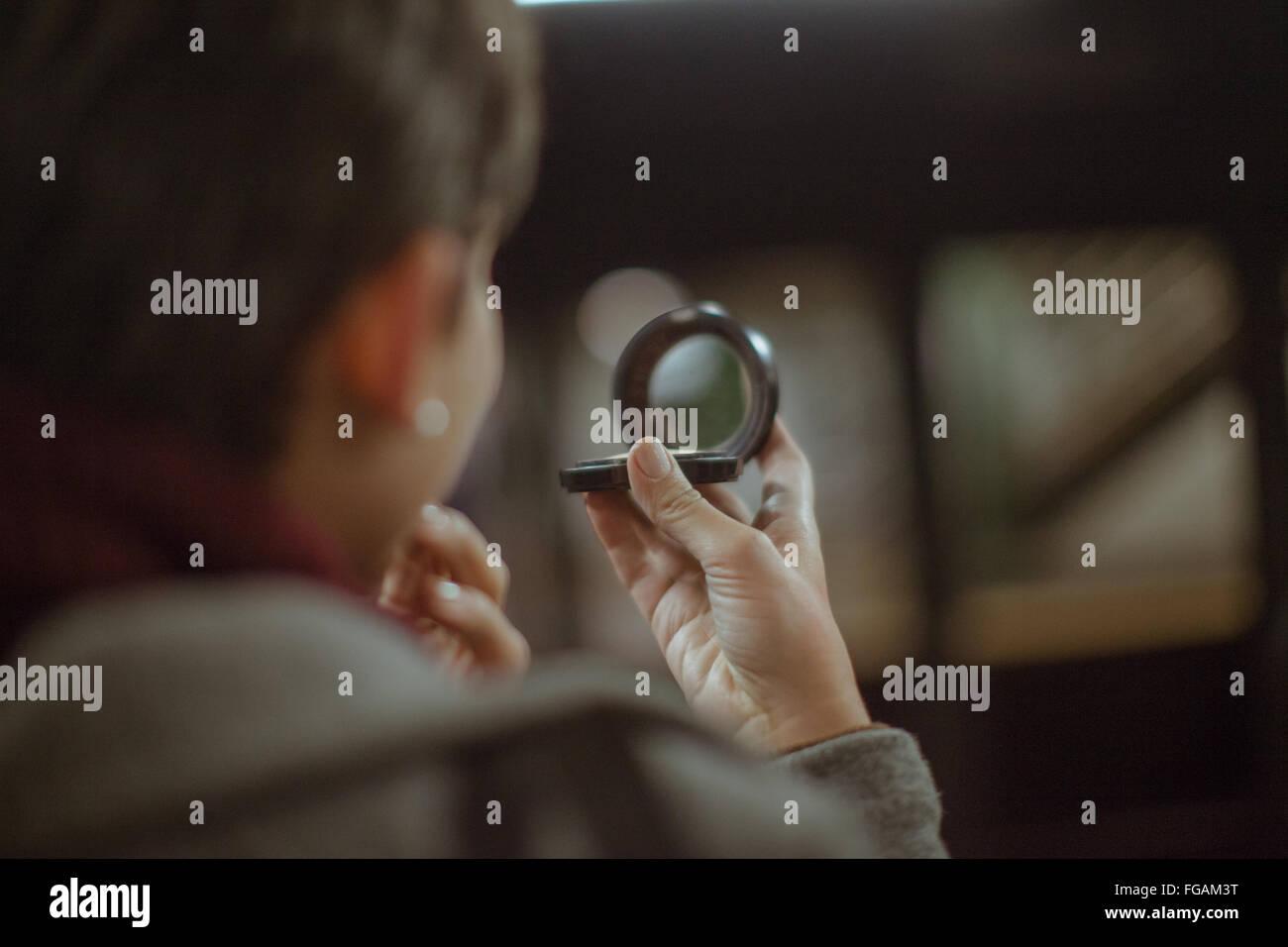 Immagine ritagliata della Donna che mantiene lo specchio a mano a casa Immagini Stock