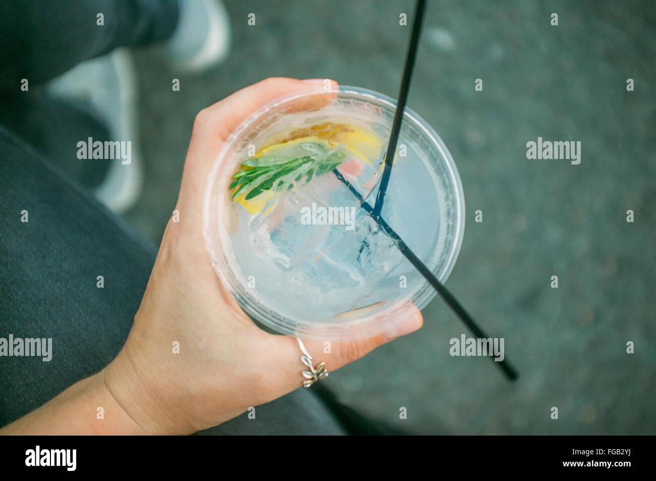Immagine ritagliata della donna tenendo il Gin Tonic Cocktail Immagini Stock