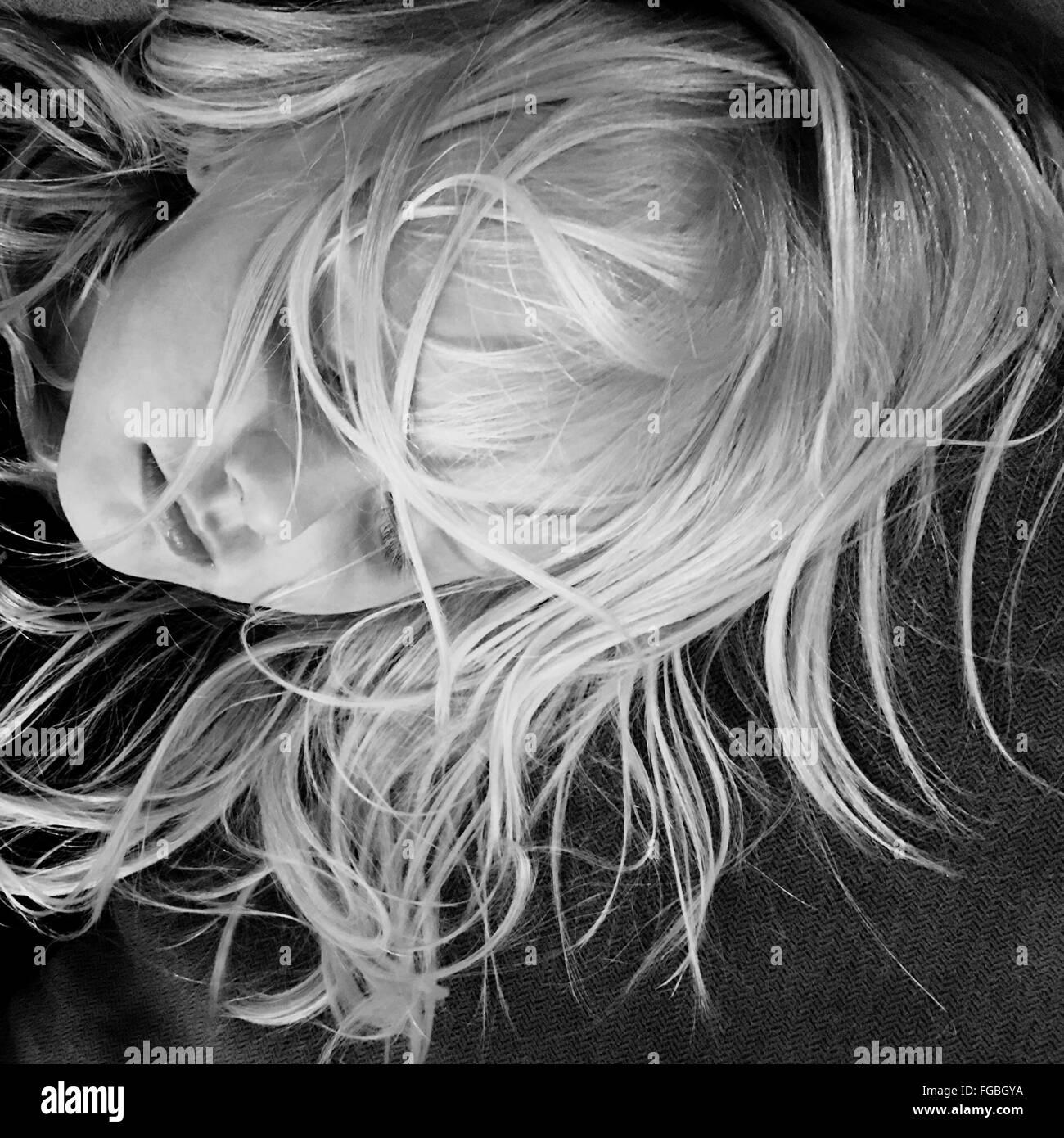 Angolo di Alta Vista della ragazza con i capelli disordinati che dorme sul letto Immagini Stock