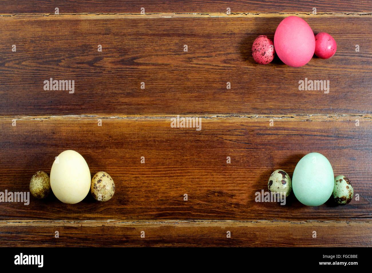 Varie le uova e uova di quaglia con carta su sfondo di legno dalla parte superiore Foto Stock