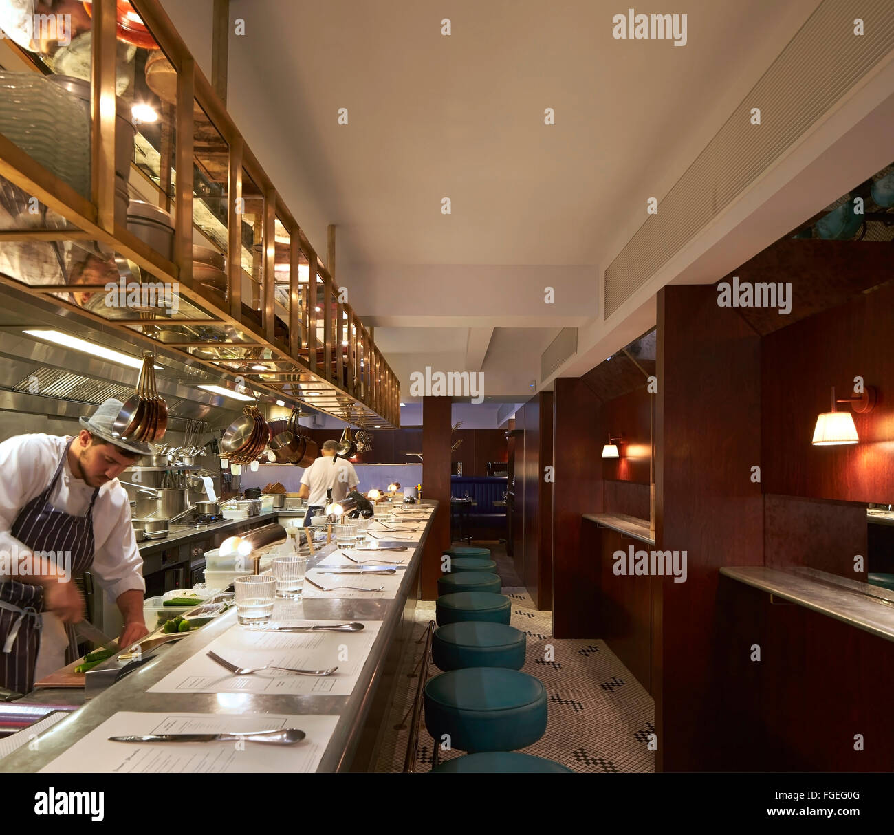 Una cucina aperta con banco bar salotto e lo chef all\'opera ...