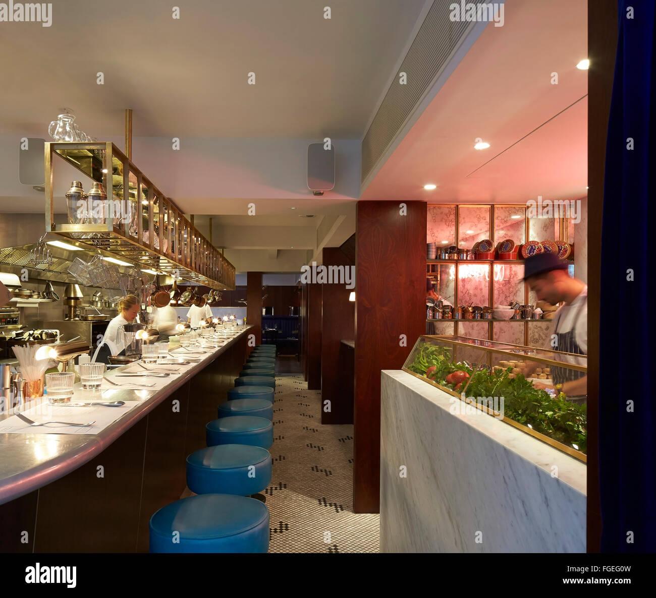 Una cucina aperta con banco bar salotto e lo chef all\'opera. Il ...