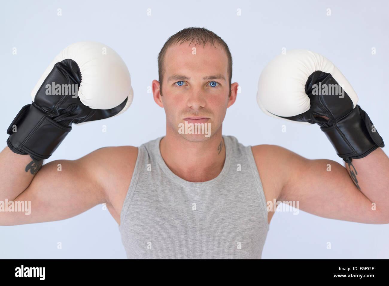 Uomo che indossa guantoni da pugilato flettendo il suo bicipite con un espressione seria di concentrazione Immagini Stock