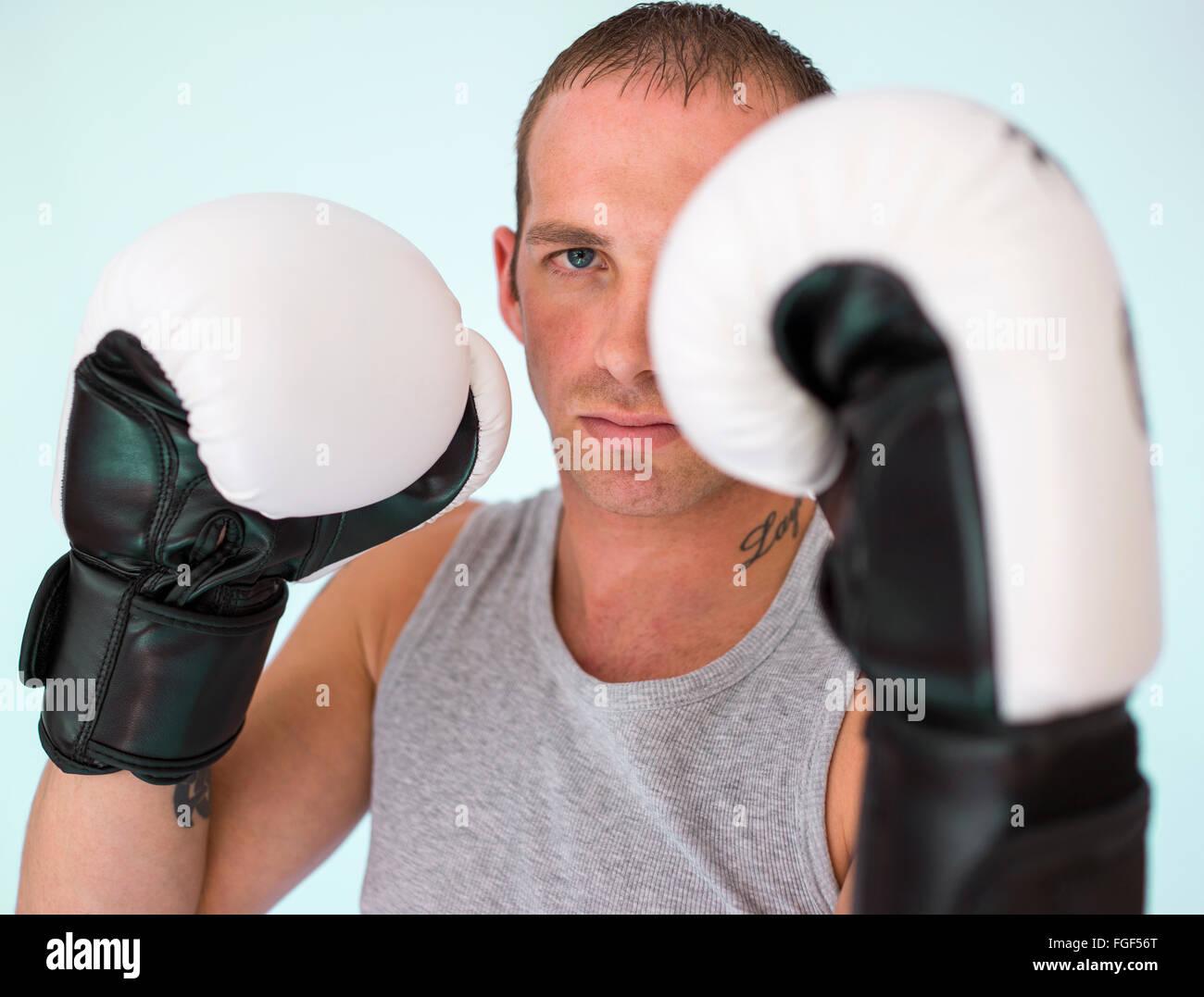 Uomo che indossa guantoni da pugilato circa per la lotta Immagini Stock