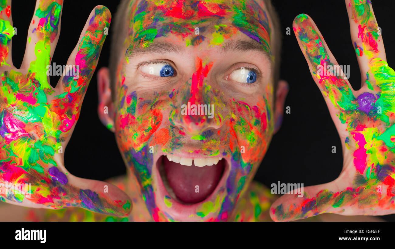Close up di un uomo il volto ricoperto in vernice colorata Immagini Stock