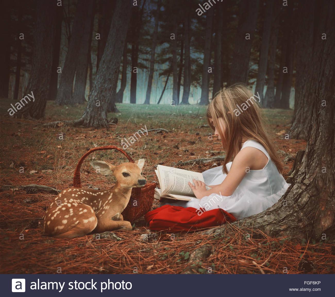 Una piccola ragazza in un abito bianco è la lettura sulla vecchia storia prenota con un bambino di cervi nei Immagini Stock