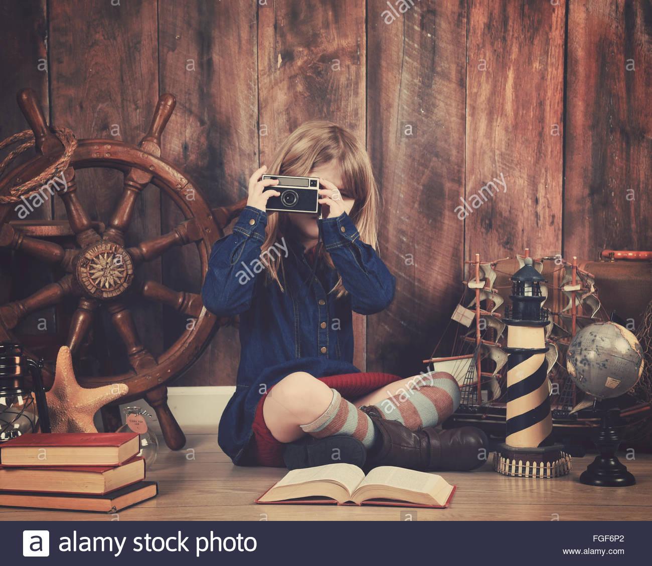 Un bambino piccolo che è in possesso di una vecchia fotocamera retrò con oggetti da viaggio in background Immagini Stock