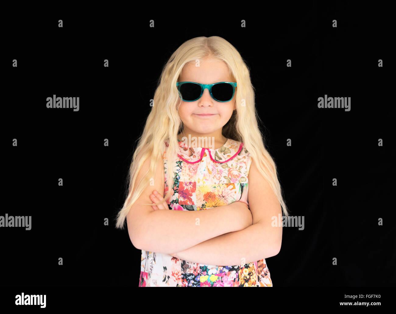 Ragazza giovane con capelli lunghi biondi indossando occhiali da sole, sorridente Immagini Stock