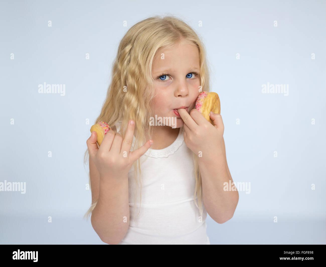 Ragazza giovane con lunghi capelli biondi di mangiare le ciambelle e leccarsi le dita Immagini Stock