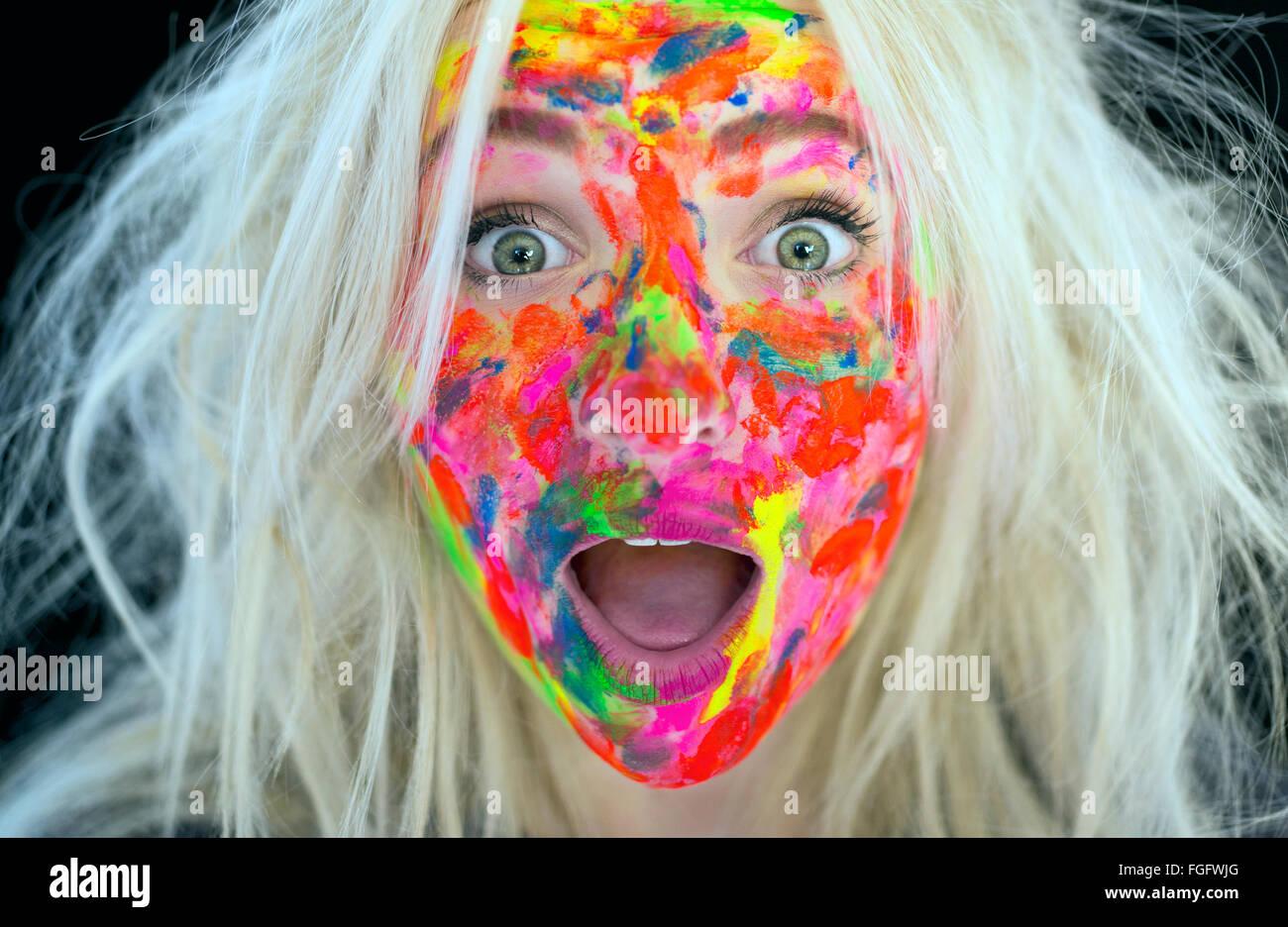 Donna con disordinati capelli biondi e la faccia coperta in multi vernice colorata con un espressione di sorpresa Immagini Stock