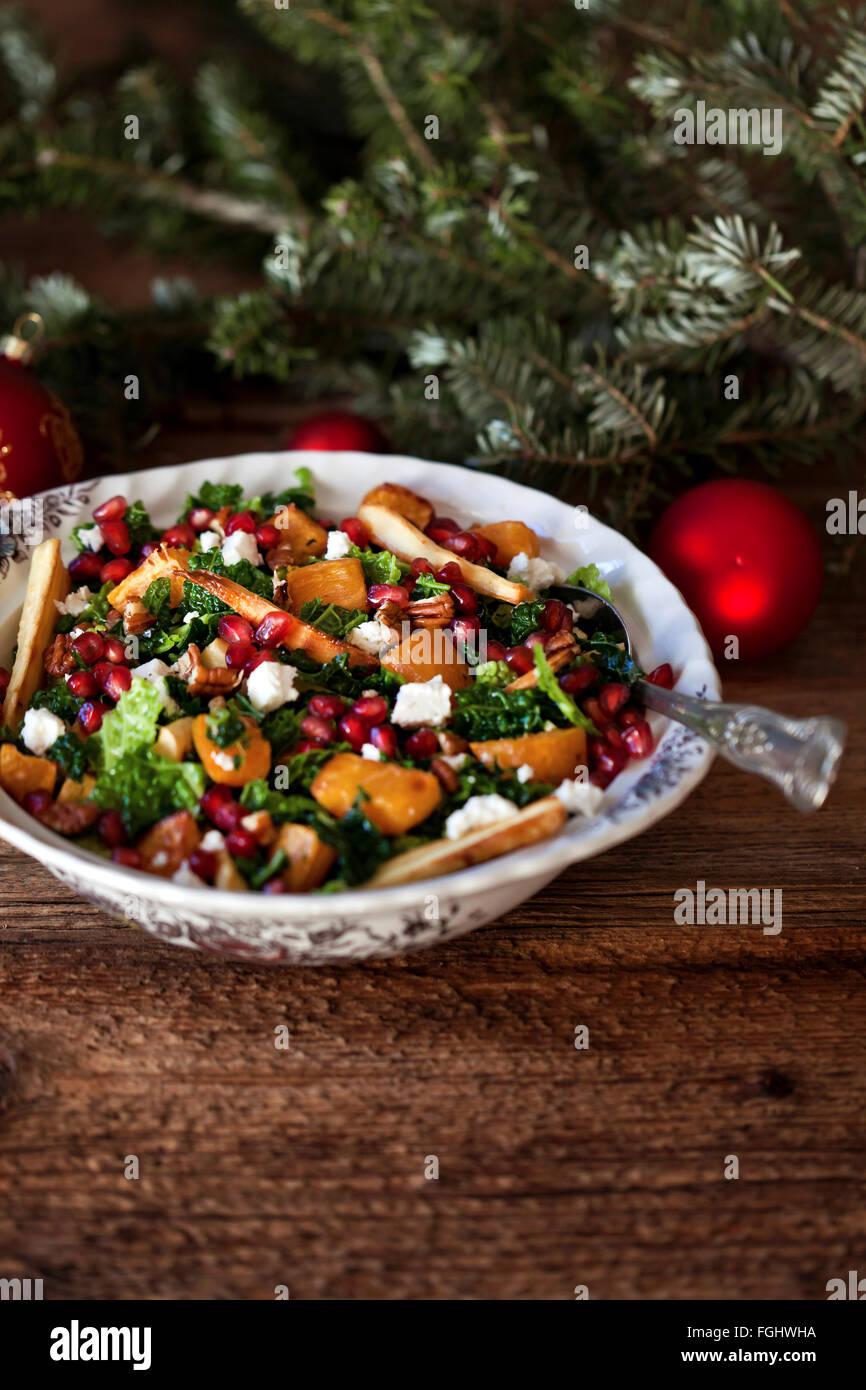 Festive kale arrosto di patate dolci e pastinaca Insalata con formaggio Feta di noci pecan e melograno in una ciotola Immagini Stock