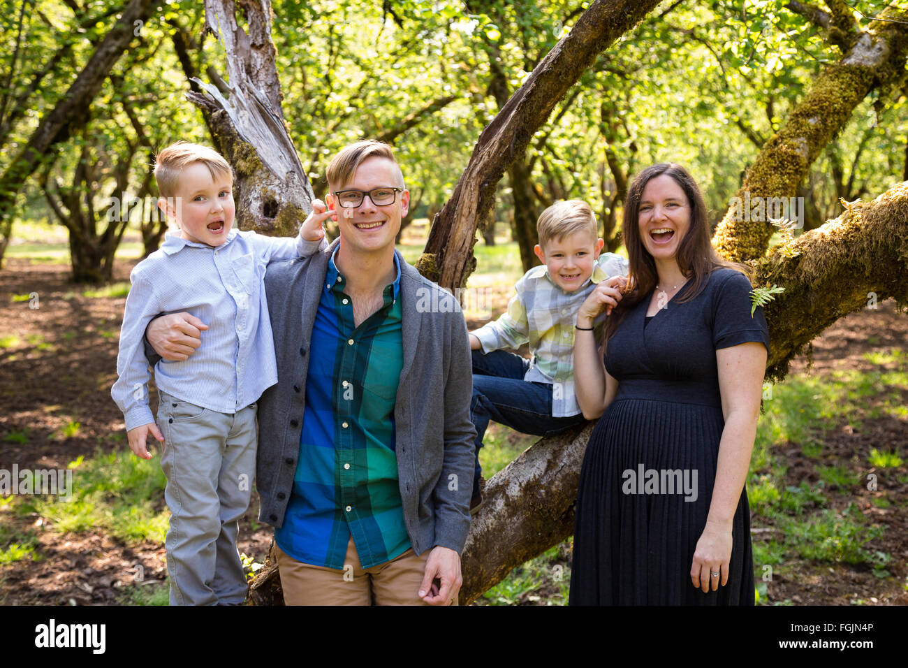Famiglia di 4 persone all'aperto in un ambiente naturale con una bella luce in un ritratto di stile di vita. Immagini Stock