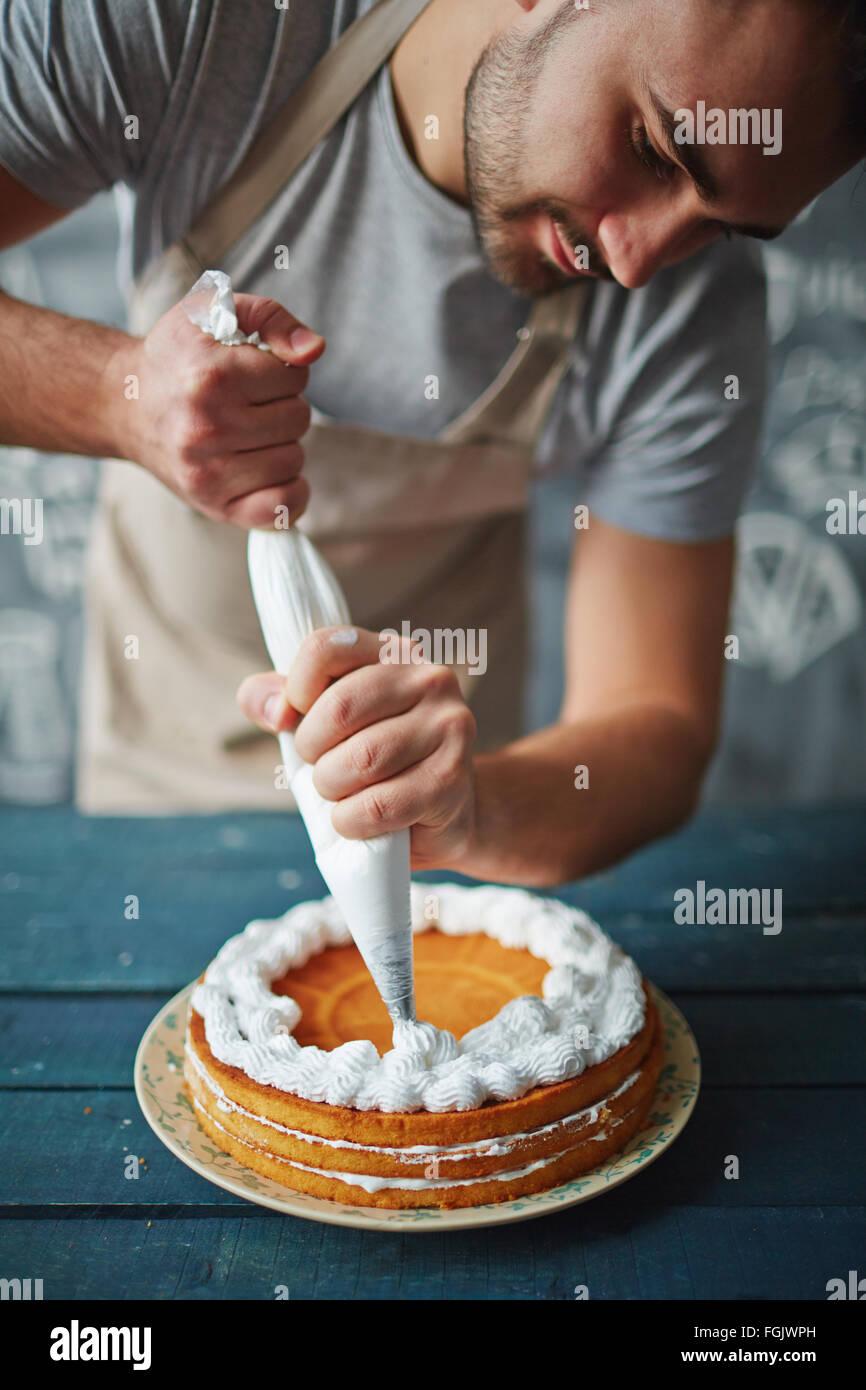 Baker decorare una gustosa torta con panna montata Immagini Stock