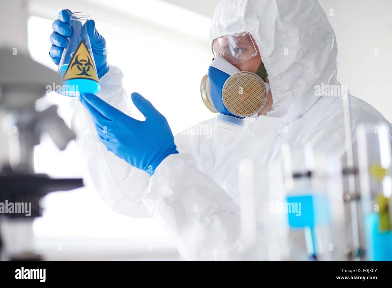Scienziato in tuta protettiva, respiratore, guanti e tubo di contenimento con sostanza fluida Immagini Stock