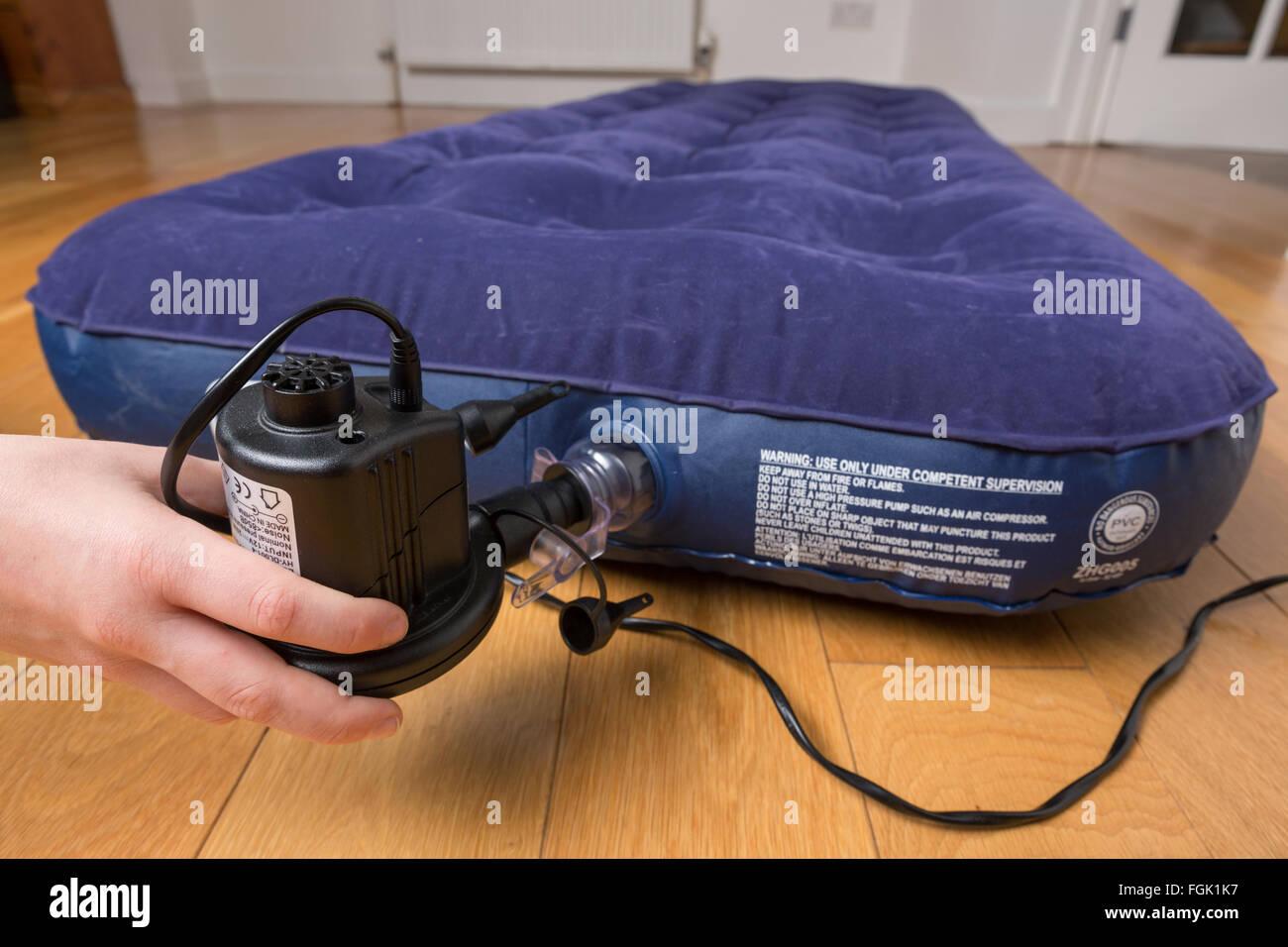 Un letto di aria essendo gonfiato con una pompa elettrica Immagini Stock