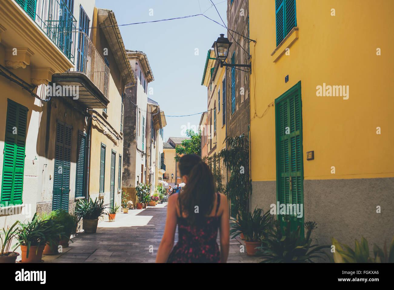 Vista posteriore della giovane donna camminare sulle strade spagnole Immagini Stock