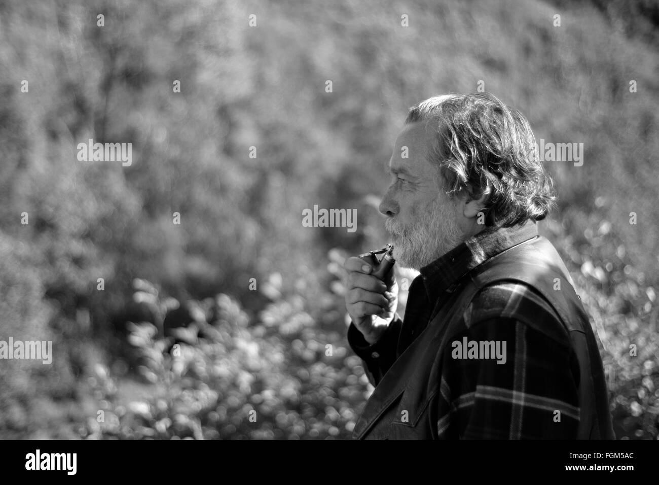 Il vecchio uomo fumare la pipa, la dipendenza del fumo è una vita lunga dipendenza ogni ora di ogni giorno. Immagini Stock