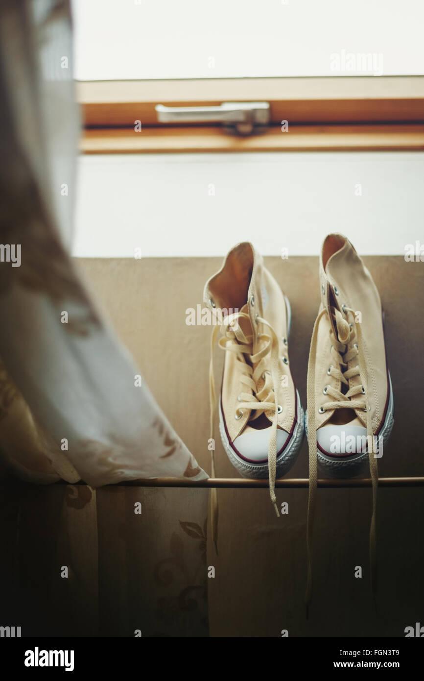 Il beige Sneakers Getting essiccato vicino alla finestra. Nei toni dell'immagine. Messa a fuoco selettiva. Immagini Stock